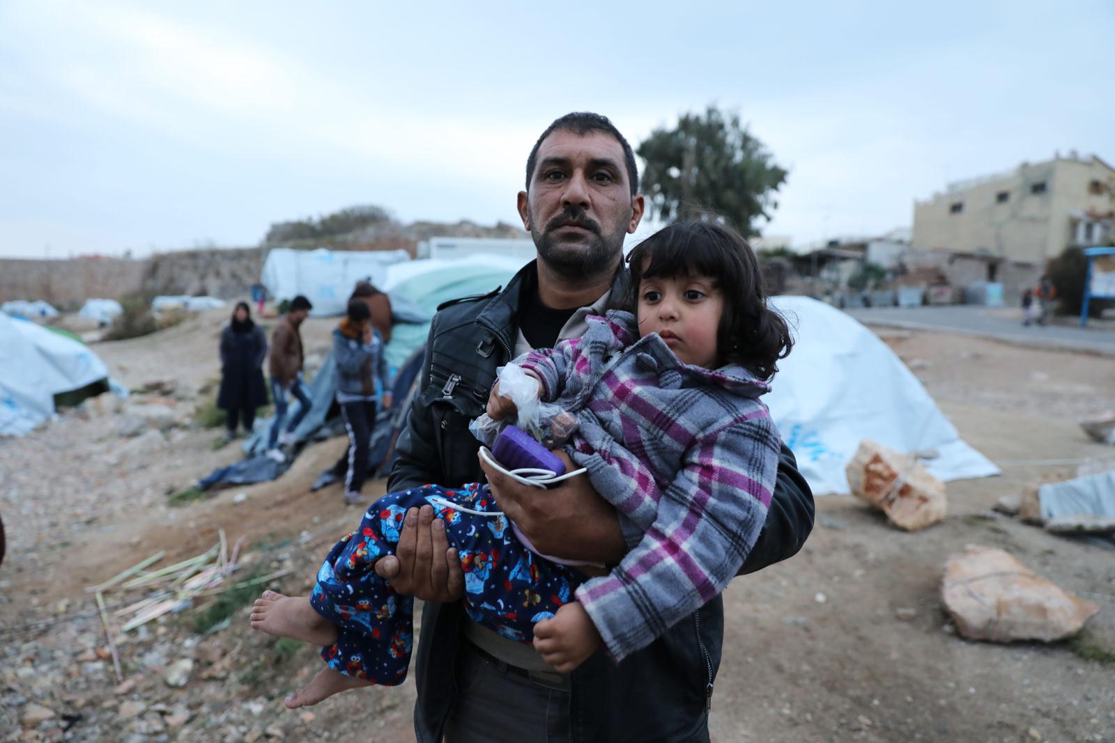 Mann mit Kind in griechischem Flüchtlingscamp